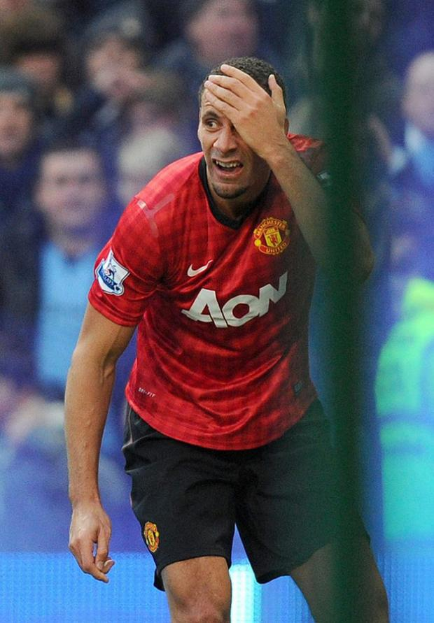 The Northern Echo: FERDINAND UNDER FIRE: Rio Ferdinand clutches his head after being hit by a coin