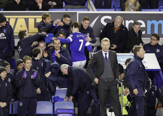 LATE SHOW: Everton's Nikica Jelavic (number 7) takes the plaudits from teammates after scoring, as manager David Moyes, right, keeps watch from the touchline