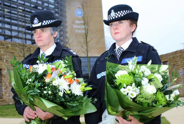 Chief Superintendent Ali Higgins and Temporary Chief Inspector Sarah Sanderson carry floral tributes