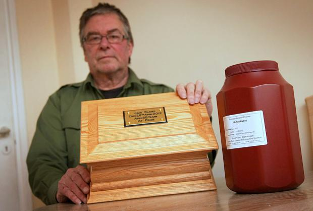 Harry Mawson with the ashes of his partner Jean Blakey in the wooden box and those of her son, Ian, in the jar.