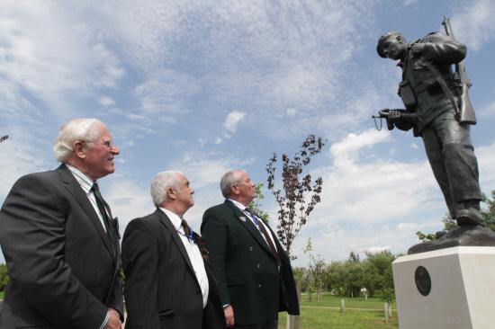 ARBORETUM STATUE UNVEILED: Captain Tony Lynn, who designed the plinth and created the first artist's impression of the statue, with former regimental signaller Keith Straughier and former bugler Richard Softley