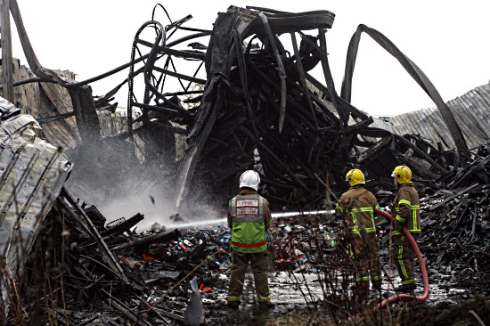 Firefighters dampen down the mangled wreckage of the warehouse