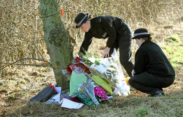 Colleagues from Greater Manchester Police lay flowers at the scene of the crash