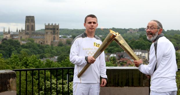 Charles Bevis passes the Olympic Flame to Matthew Burdess