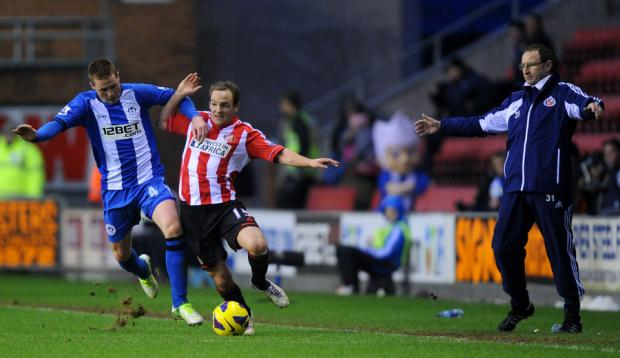 TOUCHLINE TENSION: Sunderland's David Vaughan battles for the ball with Wigan Athletic's James McCarthy, watched by Sunderland