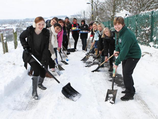 TOP CLASS: Headteacher Alison Johnson, left, clears the road to the school, assisted by parents and staff