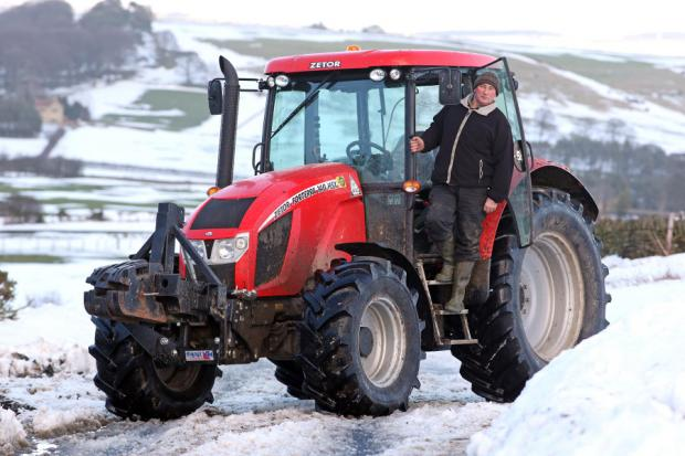 MAN ON A MISSION: Farmer Jim Smith with the tractor he used to help a fire engine stuck in the snow
