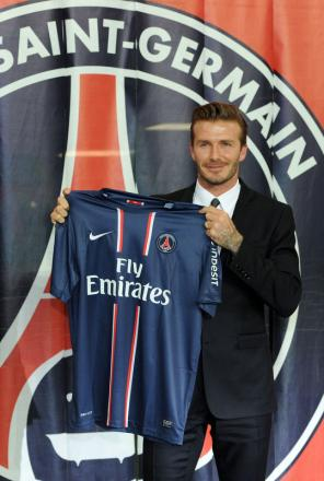 NEW COLOURS: David Beckham holds a Paris Saint Germain shirt after signing yesterday. He will wear number 32