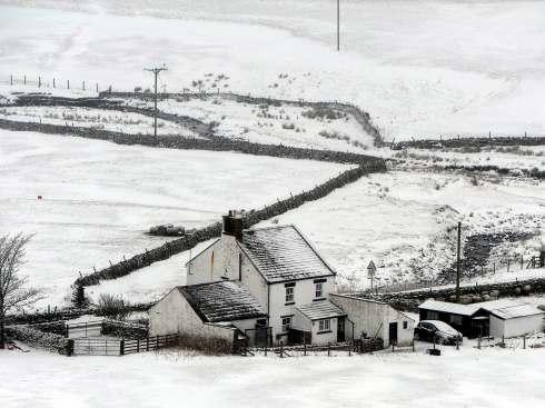 A remote home stands surrounded by snow in Harwood, upper Teesdale, County Durham this afternoon