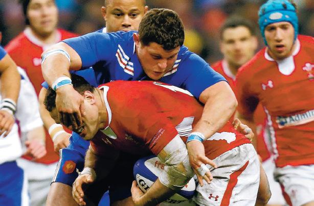 FIRM GRIP: Wales' Jamie Roberts is tackled by France's Benjamin Kayser during the RBS 6 Nations match at the Stade de France on Saturday