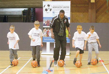 BACK HOME: Shola Ameobi runs with a group of youngsters from Walker Central Boys Club yesterday when a newly-refurbished sports centre was opened