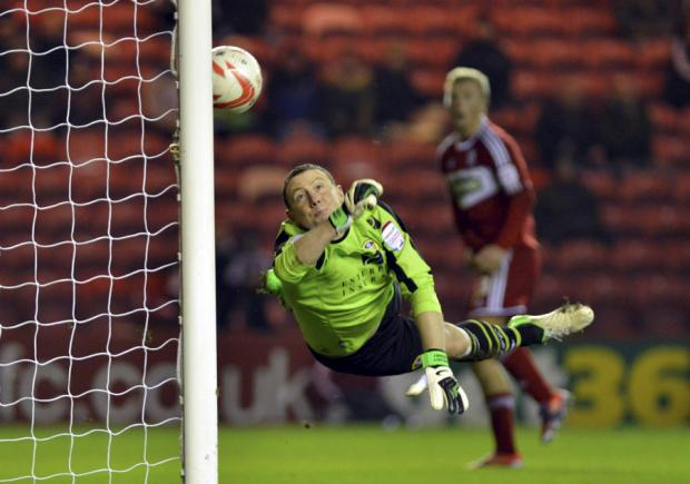 MAIN ATTRACTION: Curtis Main, in the background, watches as his header loops over Paddy Kenny in the Leeds United goal