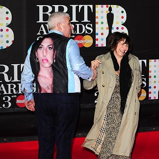 Mitch Winehouse arrives wearing a waistcoat bearing a picture of his daughter Amy