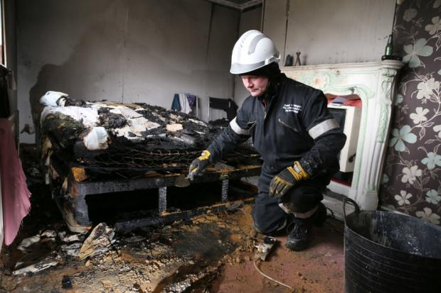 SEARCHING FOR CLUES: Student Michael Stephens examines fire damage as part of his training