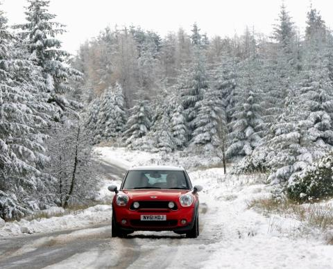 A car drives slowly on a snowy road through a beautiful Alpine scene at a forest plantation in County Durham after heavy snow showers covered northern England in a blanket of snow today.
