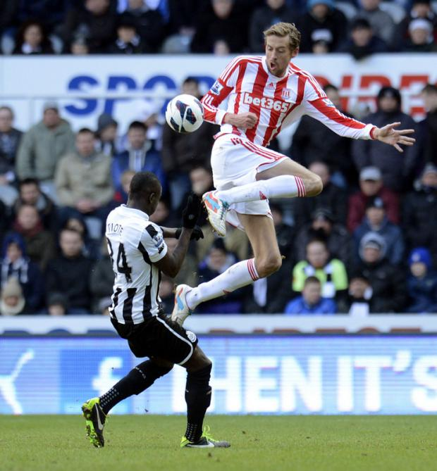 HIGH FLIER: Cheik Tiote can't hope to climb as high as Stoke's Peter Crouch