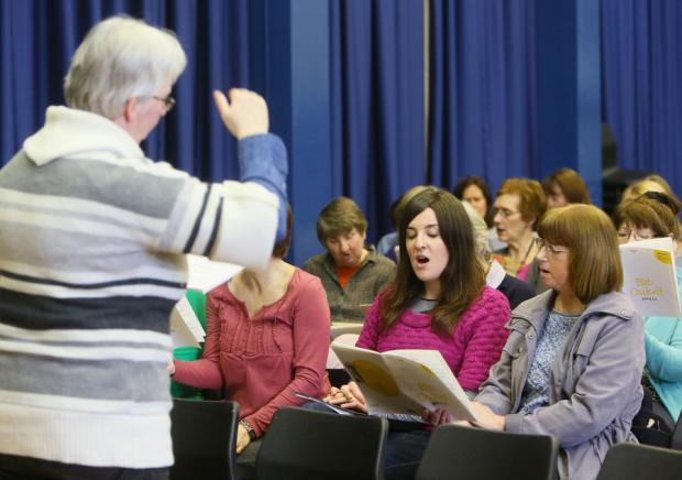 ON SONG: Reporter Lizzie Anderson, centre, takes part in choir practice for the Lindisfarne Gospels Community Choir
