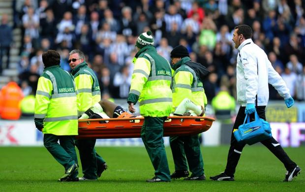 AWAITING RESULTS: Newcastle's Massadio Haidara is stretchered off during Sunday's defeat at Wigan - following a horror tackle by Callum McManaman, but one that was defeated by Chairman Dave Whelan