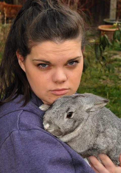 Melissa Richardson hugs one of her pet rabbits after a police dog mauled one to death.