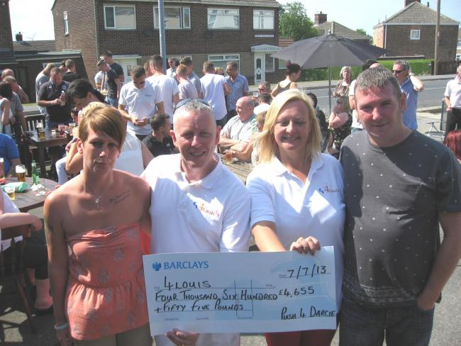 CHEQUE PRESENTATION: Bob and Tracey McGurrell (centre) accept cheque from 4Louis