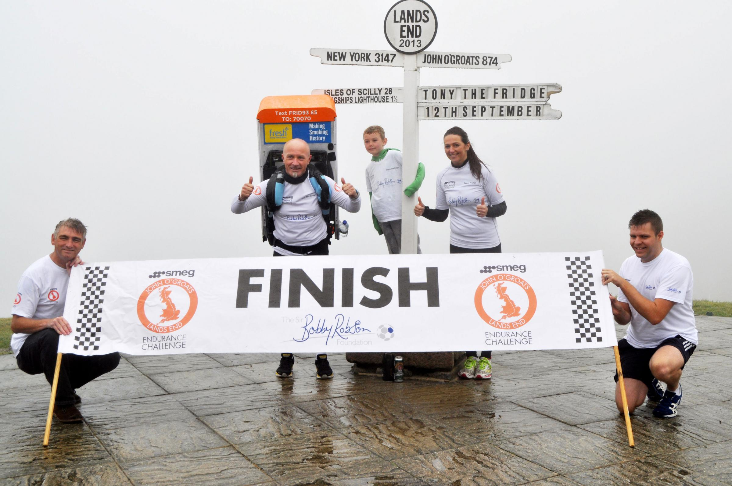 Tony Phoenix-Morrison, with his support team, completing his John O'Groats to Lands End run with a 42.5kg fridge on his back.