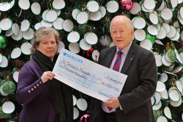 Cornmill shopping Centre promotions manager Sam Gore with the cheque for £6,00 raised from the Giving Tree, accepted by Alasdair McConachie, president of the Board of Trustees for St Teresa's Hospice