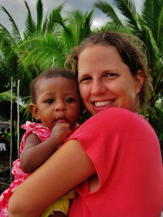 Dr Beth Lewis gives five month old Maggie, one of her 30,000 patients, a hug at her jungle hospital in Papua New Guinea