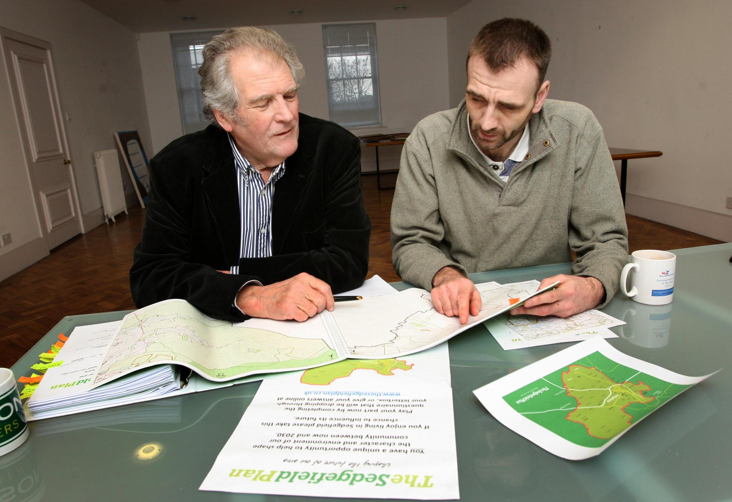 Business man David Bowles (l) and Chris Lines (r) look over the plans for the Sedgefield Plan