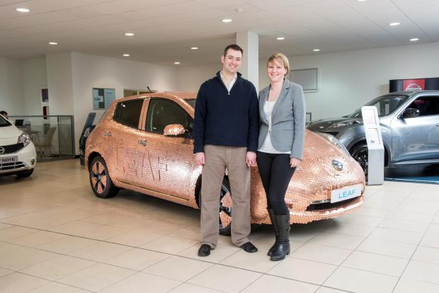 Brett and Liz Garner in front of a Nissan leaf covered in coins