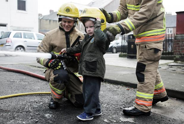 WATER LARK: Luca Johnson, three, with fire fighter Ben Dalton at Lowson Street Pre-School