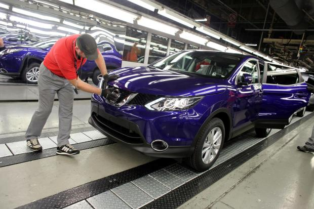 A Nissan worker fits a badge to a new Qashqai at the firm's Sunderland plant