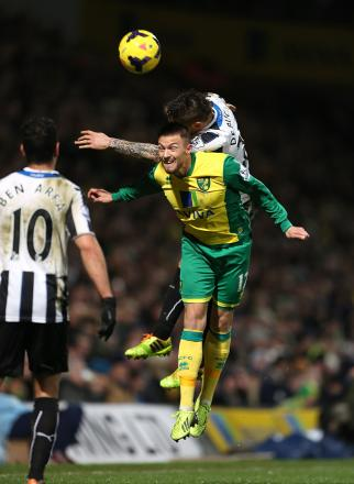 AERIAL BATTLE: Norwich City's Anthony Pilkington and Newcastle United's Mathieu Debuchy vie for the ball last night