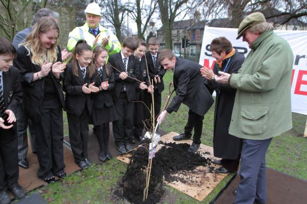 Head Boy George Benson, 16, shovels earth into the planted tree at King James 1 Academy watched by children and ViPs at the ceremony