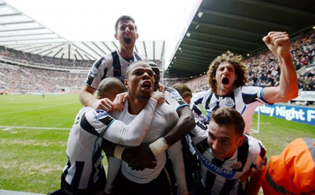 LATE SHOW: Loic Remy is mobbed by team-mates after scoring a last-minute winning goal for Newcastle against Aston Villa yesterday