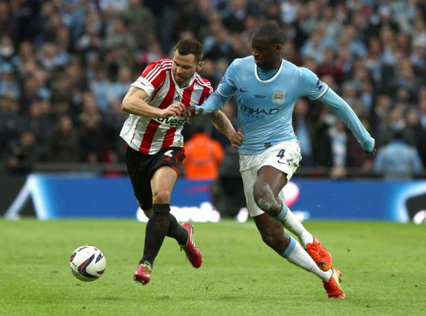 TOURE TUSSLE: Phil Bardsley tries to shrug off the attentions of Yaya Toure