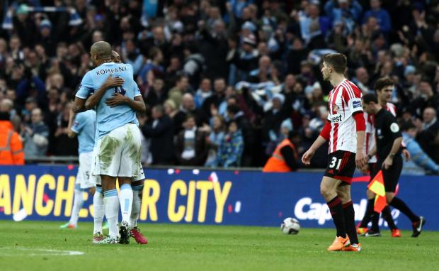 MIXED FORTUNES: Sunderland striker Fabio Borini, scorer of the first goal, looks on as Vincent Kompany hugs Samir Nasri, who had put Manchester City into a 2-1 lead