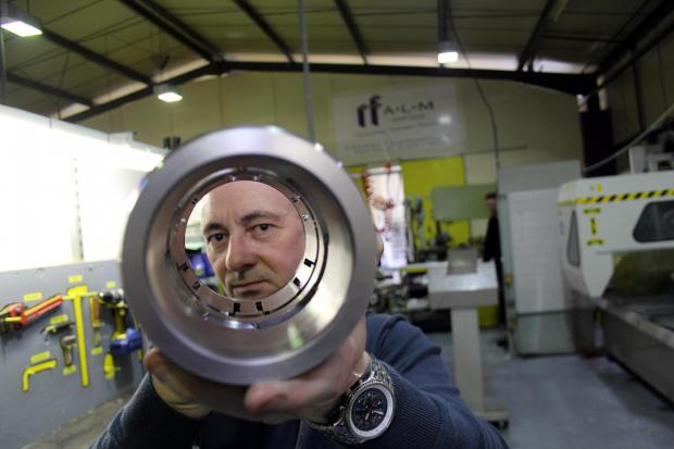 ALM's quality engineer Trevor Wright holds a component, made by the firm's new £160,000 lathe, for the oil and gas sector