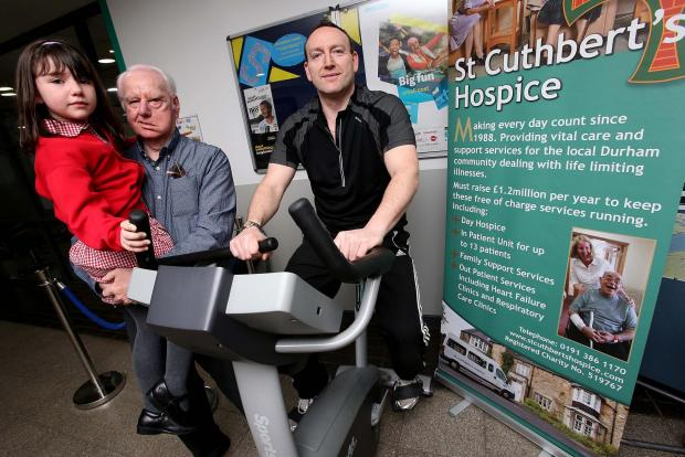 James Hewitt takes part in the static bike ride challenge to help raise money for the St Cuthbert's Hospice watched by his daughter Jessica and dad George