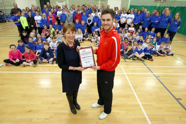 OFFICIAL RECOGNITION: Helen Letts, Sedgefield Harriers Club Mark co-ordinator, and John Stacey, club and coach support officer from England Athletics, with members of the harriers gather in Sedgefield Community College Sports Hall for the Club Mark award