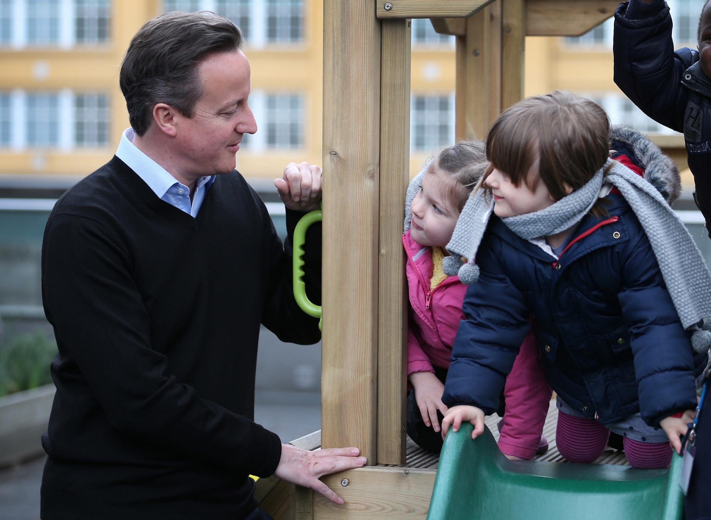 Children talk to Prime Minister David Cameron during a visit to the Coin Street nursery in London, as the government have announced a new tax-free childcare allowance