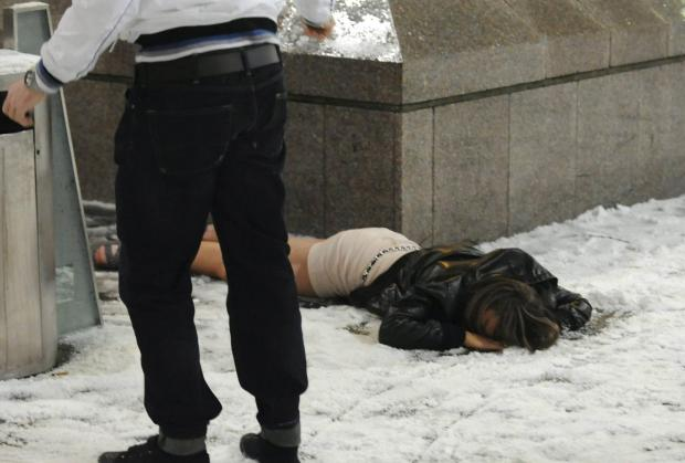 A reveller in Newcastle on New Year's Eve lies on the icy pavement after a night on the town