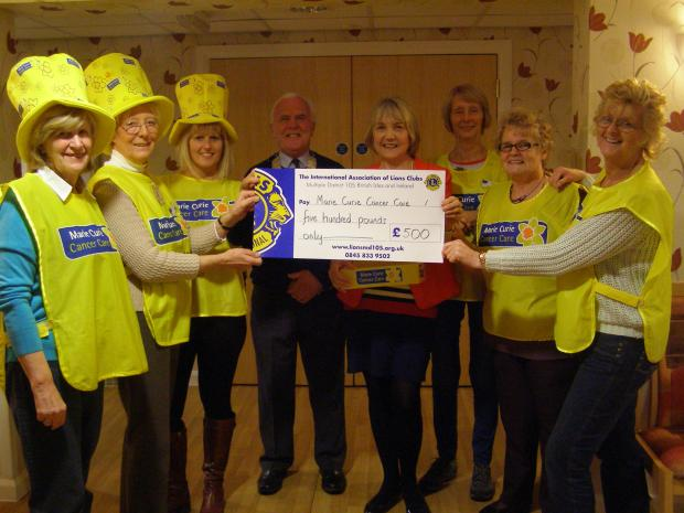 Members of the Darlington Lions hand over the £500 raised to Marie Curie