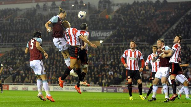 POWERING HOME: Andy Carroll, the Gateshead-born former Newcastle United striker, towers above Wes Brown and John O'Shea to give West Ham the lead