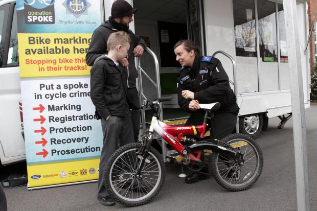 PCSO Stephanie Field marks up nine-year-old Joshua Smith's bike at a bike marking session at Corporation Road Primary School