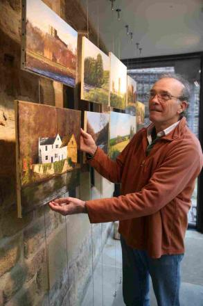 Artist Peter Hemming hangs his work at the Heritage Centre in Durham City.