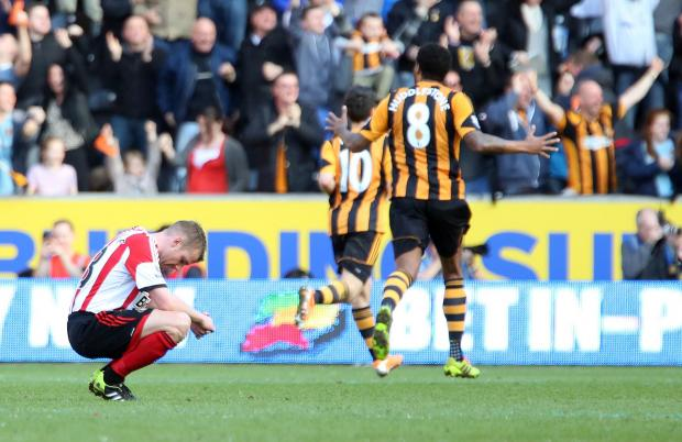 EMOTIONAL MOMENT: As Hull players celebrate their third goal, Sunderland's Lee Cattermole drops to his knees after his mistake led to their goal