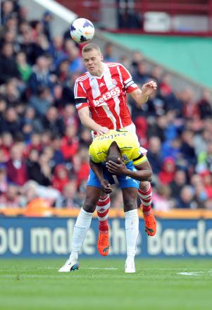 HEADS FIRST: Stoke City's Ryan Shawcross, top, and Newcastle United's Shola Ameobi battle for the ball