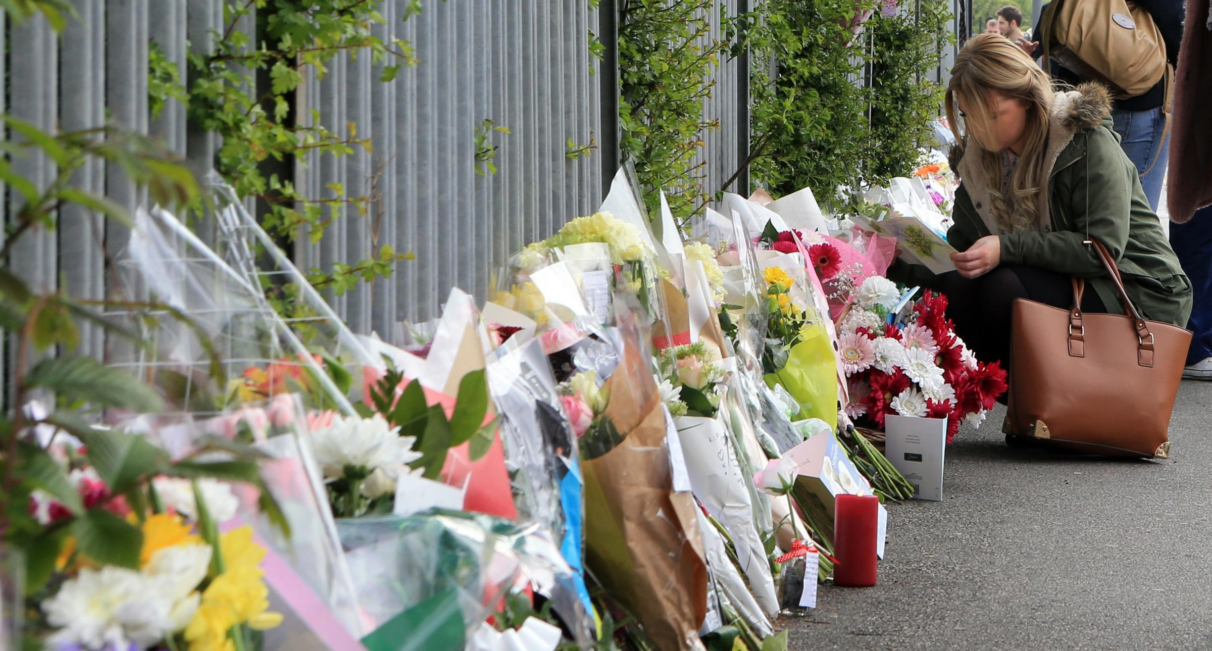 People look at the floral tributes outside Corpus Christi Catholic College