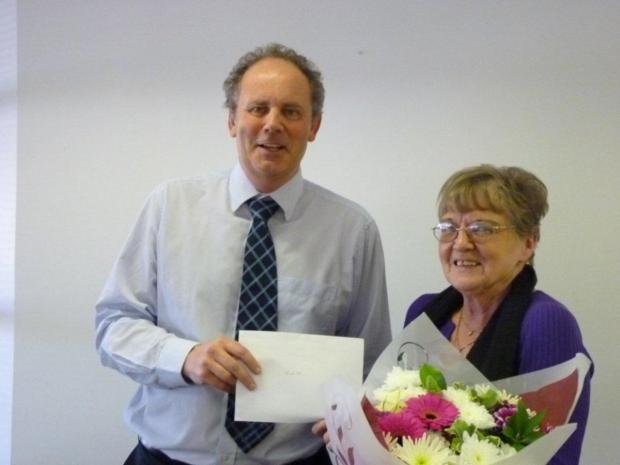 HAPPY DAY: Judith Madrell being presented with her gift and flowers by colleague Tony Spaldin (correct)