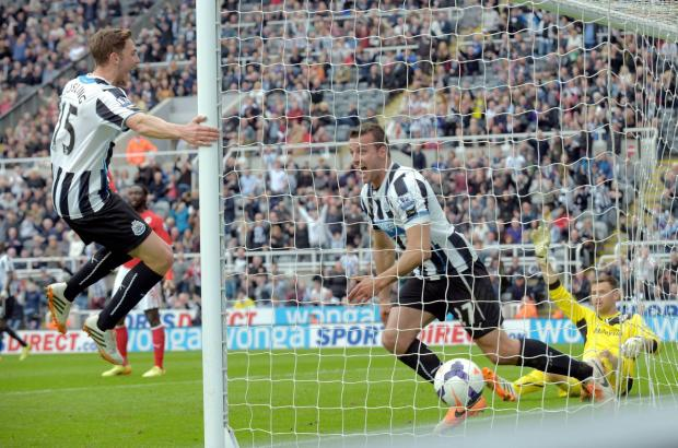 JUMPING FOR JOY: Dan Gosling swings around on the post after Steven Taylor scored at St James' Park